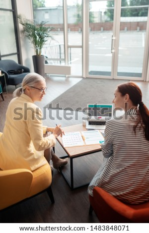 Businesswoman and customer. Back view of two businesswomen sitting in front of a laptop in the office building while talking to each other #1483848071