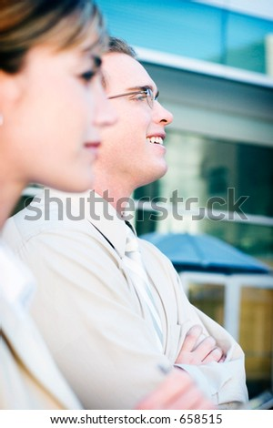 businesswoman and man look together towards the right