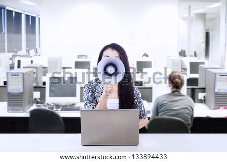 Businesswoman announce meeting at the office using megaphone - stock photo