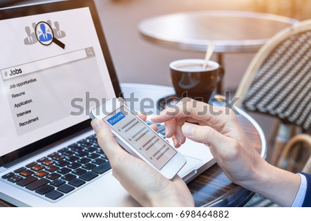 Businesswoman at cafe searching for job and career opportunities online with smartphone and laptop computer and sending resume for application, HR concept, close-up on hands #698464882