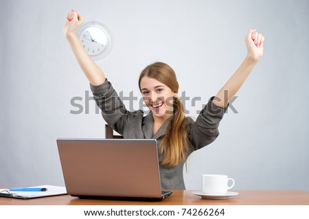 Businesswoman at desk with arms thrown up, while looking at camera