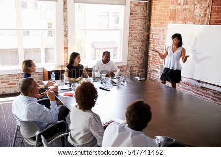 Businesswoman At Whiteboard Giving Presentation In Boardroom #547741462
