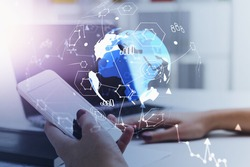 Businesswoman at workplace checking smartphone. Abstract hologram planet earth and social media chart background symbolizing international human resources business. HR networking.