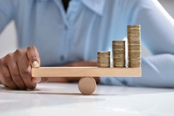 Businesswoman Balancing Stacked Coins With Finger On Wooden Seesaw