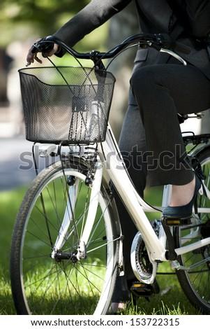 Businesswoman biking, unrecognizable person