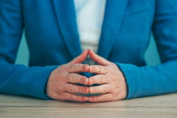 Businesswoman body language for confidence and self-esteem, hands with steepled fingers on office desk