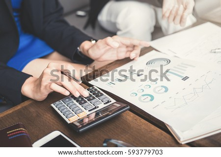 Businesswoman calculating and discussing financial documents - assessment and evaluation concepts #593779703