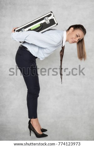 businesswoman carries a heavy suitcase on her back #774123973