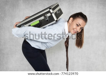 businesswoman carries a heavy suitcase on her back, close up #774123970