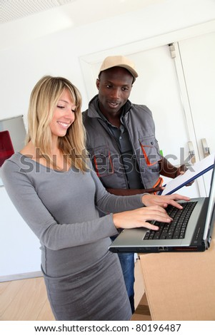 Businesswoman checking order with delivery man