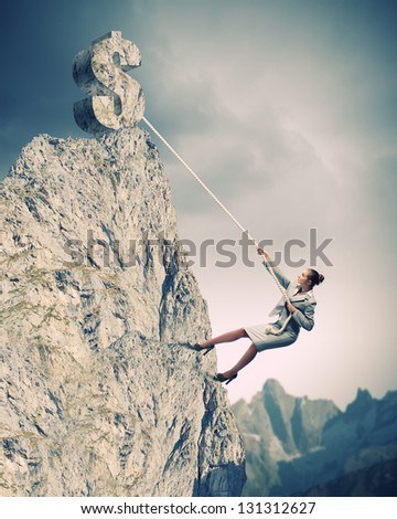 businesswoman climbing mountain with dollar on top