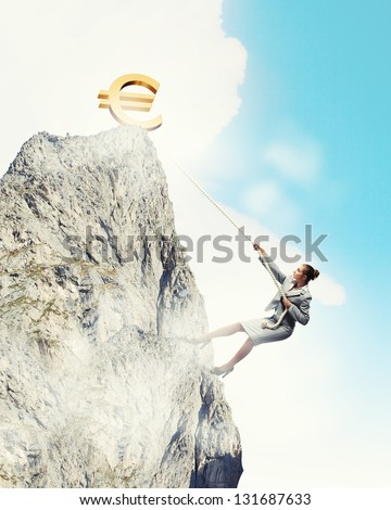businesswoman climbing mountain with euro on top