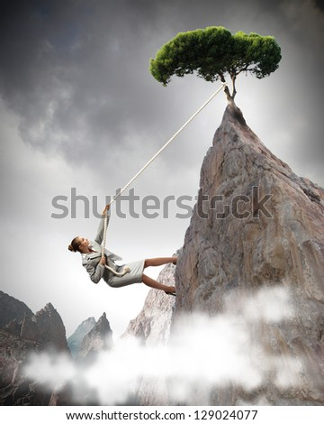 businesswoman climbing steep mountain with tree on top hanging on rope