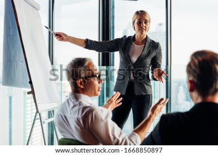 Businesswoman coach speaker wear suit give blank flipchart presentation, Speaker presenter consulting training persuading employees client group, Business meeting, seminar, presentation concept.