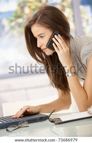Businesswoman concentrating on work, using computer and cellphone in office.?