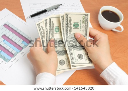 Businesswoman counting money at her workplace