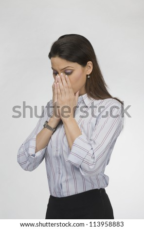Businesswoman covering her face with her hands