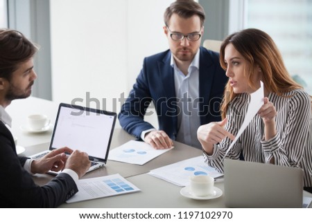 Businesswoman criticizes subordinate work, pointing out mistake in document. Business partners discuss terms of contract. Colleagues discuss business strategy.