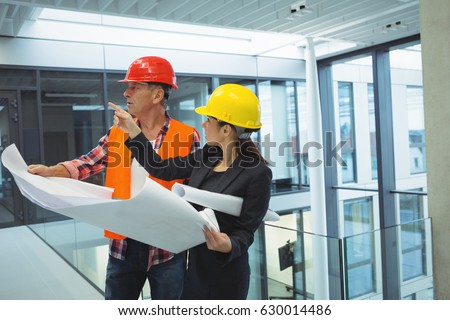 Businesswoman discussing over blueprint with an architect in office #630014486