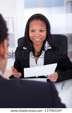 Businesswoman Discussing With His Co-worker In Office