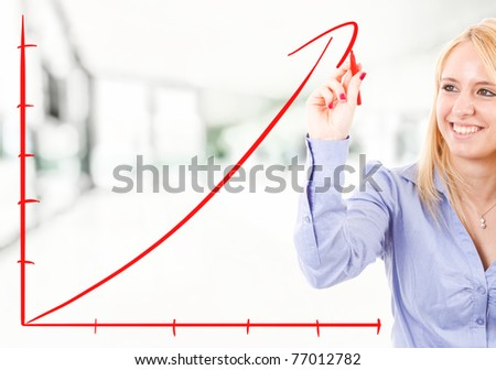 Businesswoman drawing a rising arrow, representing business growth.