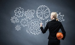 Businesswoman draws gears mechanism on blackboard. Back view woman in business suit with safety helmet. Company presentation of mechanical engineering and project management. Great business solution