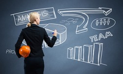 Businesswoman draws various business diagram on chalkboard. Back view woman with safety helmet and pen in hands. Speaker standing near blackboard with analytics. Creative business data visualization.
