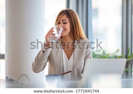 Businesswoman drinking a glass of water at her desk in the office. Young woman working in her offfice. Woman drinking water from glass in the office in the morning with sunlight