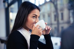 Businesswoman drinking coffee in cafe and looking away