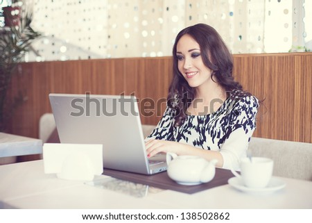 Businesswoman drinking tea and using computer in a coffee