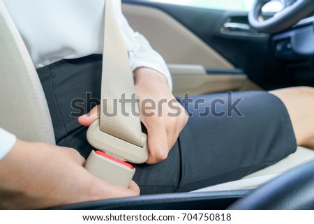 Businesswoman fastening seat belt in car before driving #704750818
