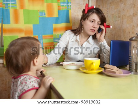 businesswoman feeding baby and  speak by mobile at kitchen in morning