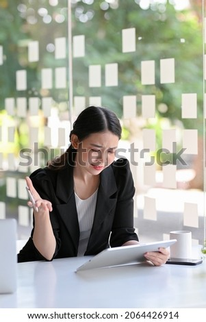 Businesswoman feeling upset and unsatisfied with the project result, looking at tablet touchpad screen in office.