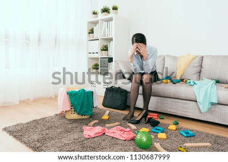 businesswoman feels frustration to see the mess made from her kids after she back from work