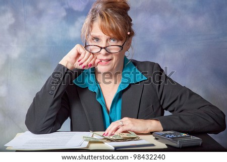 Businesswoman frustrated with accounting, paper, and money before her