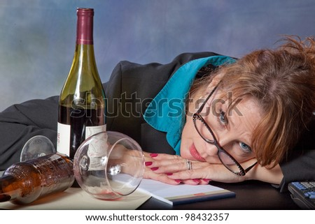 Businesswoman frustrated with accounting, paper, and money before her and her wine and beer bottles with her marking her frustration
