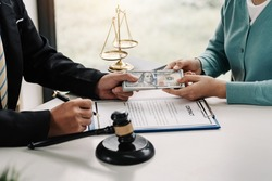 Businesswoman gave the lawyer money to help with the case and sign the contract at the office.