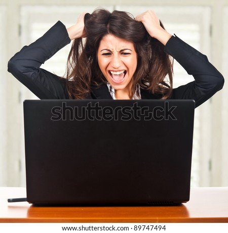 Businesswoman getting crazy in front of her laptop - stock photo