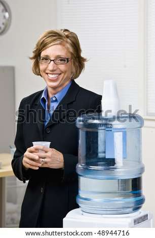 Businesswoman getting water from water cooler