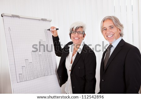 Businesswoman giving a presentation to her male colleague drawing a bar graph on a board as they analyze performance and discuss strategy
