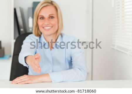 Businesswoman giving hand in her office #81718060