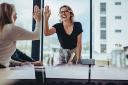 Businesswoman giving high five to colleague in meeting. Happy business professionals having meeting in office conference room.