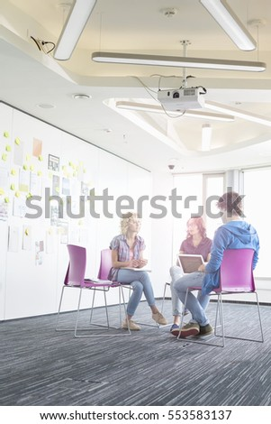 Businesswoman giving presentation to colleagues in creative office space #553583137