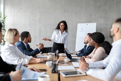 Businesswoman Giving Speech On Corporate Meeting Making Business Presentation For Colleagues Standing Near Blackboard In Modern Office. Female Employee Presenting Business Startup