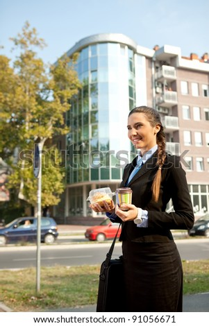 businesswoman  going on work with breakfast in  hands