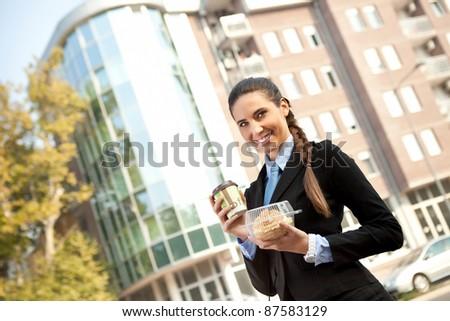 businesswoman going to work with breakfast in hand, outdoor