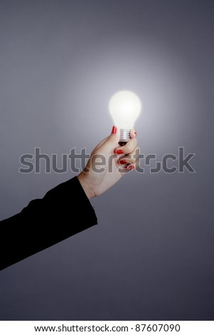 Businesswoman hand holding a light bulb isolated on grey