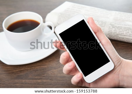 businesswoman hand holding a phone with isolated screen against the background of the table in the office