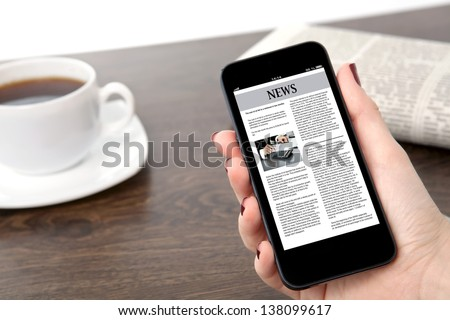 businesswoman hand holding a touch phone with business news on a screen against the background of the table in the office