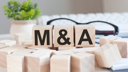 Businesswoman hand holding M and A word with wooden cube block. mergers and acquisitions, Information, Communication Concepts